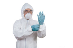 Asian Chinese scientist in protective wear putting on gloves Stock Photos