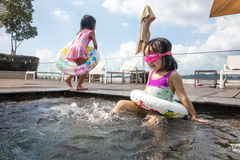 Asian chinese sister plyaing at the outdoor swimming pool Stock Photo