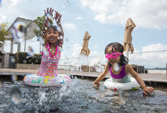 Asian chinese sister plyaing at the outdoor swimming pool Stock Photos