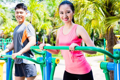 Asian Chinese sport friends in outdoor fitness gym Stock Photos