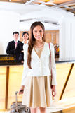 Asian Chinese woman arriving at hotel front desk. Asian Chinese women arriving at front desk of luxury hotel in business clothes with trolley Royalty Free Stock Image
