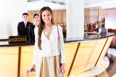 Asian Chinese woman arriving at hotel front desk. Asian Chinese women arriving at front desk of luxury hotel in business clothes with trolley Stock Photo
