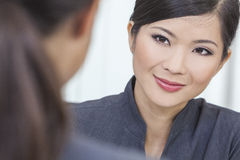 Asian Chinese Woman or Businesswoman in Meeting. Portrait of a beautiful young Asian Chinese women or businesswoman in office meeting with female colleague stock photo