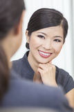 Asian Chinese Woman or Businesswoman in Meeting. Portrait of a beautiful young Asian Chinese women or businesswoman in office meeting with female colleague Royalty Free Stock Photos