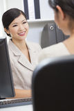 Asian Chinese Woman or Businesswoman in Meeting. Portrait of a beautiful young Asian Chinese women or businesswoman in office meeting with female colleague Royalty Free Stock Photo