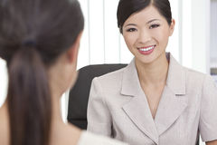 Asian Chinese Woman or Businesswoman in Office. Beautiful young Asian Chinese women or businesswoman in smart business suit sitting at a desk in an office having Royalty Free Stock Images