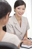 Asian Chinese Woman or Businesswoman in Office. Beautiful young Asian Chinese women or businesswoman in smart business suit sitting at a desk in an office having Stock Photos