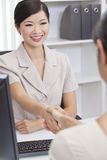 Asian Chinese Woman or Businesswoman Shaking Hands. Beautiful young Asian Chinese women or businesswoman in smart business suit sitting at a desk in an office Royalty Free Stock Image