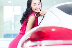 Asian Chinese woman buying SUV car. Marveling at the beauty of the auto Stock Image