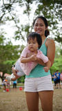 Asian chinese woman carrying her toddler Royalty Free Stock Photo