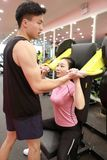 Asian chinese woman in gym lifting weights. Personal trainer helping women at gym,Woman in gym try with dumbbells Stock Image