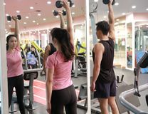 Asian chinese woman in gym lifting weights. Personal trainer helping women at gym,Woman in gym try with dumbbells Royalty Free Stock Image