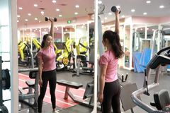 Asian chinese woman in gym lifting weights. Woman in gym try with dumbbells Royalty Free Stock Images