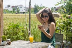 Asian Chinese woman on her 20s or 30s smiling having fun using internet on mobile phone shooting selfie or chatting drinking orang Stock Photos
