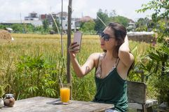 Asian Chinese woman on her 20s or 30s smiling having fun using internet on mobile phone shooting selfie or chatting drinking orang Stock Images