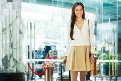 Asian Chinese Woman at hotel entrance arriving. Asian Chinese woman arriving at luxury hotel in business clothes with trolley entering through a glass door into royalty free stock photography