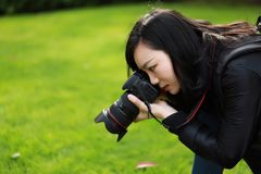 Portrait of a nature photographer covering her face with camera in a spring park Stock Photo