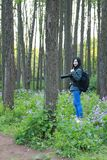Portrait of a Asian Chinese nature woman photographer look at her camera screen in a spring park forest , with good hand gesture royalty free stock photography