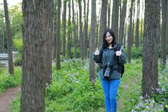 Portrait of a Asian Chinese nature woman photographer look at her camera screen in a spring park forest , with good hand gesture stock photos