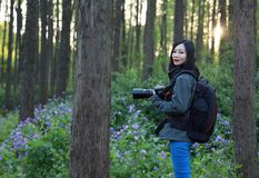 Nature travel photographer woman. Asian chinese Woman Nature travel photographer woman taking pictures in forest during hiking trip. Beautiful happy smiling Royalty Free Stock Image
