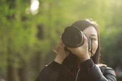 Portrait of a nature photographer covering her face with camera in a spring park Stock Photos