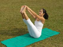 Asian chinese woman practising yoga outdoors. Asian chinese woman practising yoga on a outdoor grass patch Royalty Free Stock Images
