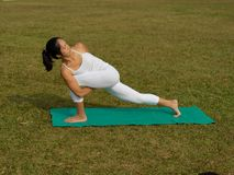 Asian chinese woman practising yoga outdoors. Asian chinese woman practising yoga on a outdoor grass patch Royalty Free Stock Image