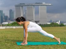 Asian chinese woman practising yoga outdoors in Singapore Royalty Free Stock Photo