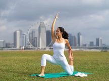 Asian chinese woman practising yoga outdoors in Singapore. Outdoor image of an asian chinese woman practising yoga with the landscape of singapore in the Stock Images