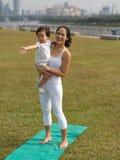 Asian chinese woman practising yoga outdoors with young baby gir. Asian chinese women practising yoga outdoors watched by a baby girl Stock Photography