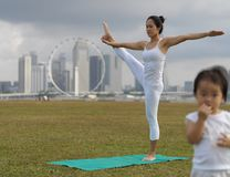 Asian chinese woman practising yoga outdoors with young baby girl royalty free stock images