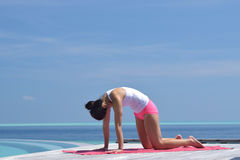Asian chinese woman practising yoga by the sea Royalty Free Stock Photography