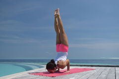 Asian chinese woman practising yoga by the sea Stock Photo