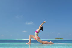 Asian chinese woman practising yoga by the sea Royalty Free Stock Photo
