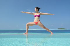 Asian chinese woman practising yoga by the sea royalty free stock images