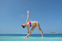 Asian chinese woman practising yoga by the sea Stock Images