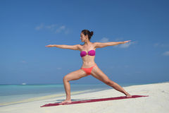 Asian chinese woman practising yoga by the sea Stock Photos