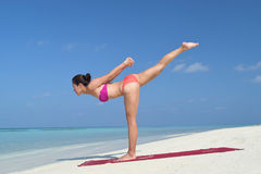 Asian chinese woman practising yoga by the sea Royalty Free Stock Image