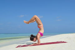 Asian chinese woman practising yoga by the sea Stock Photography