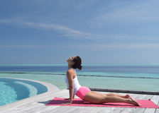 Asian chinese woman practising yoga by the sea Royalty Free Stock Photos