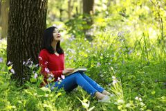 Beautiful young girl reading book while sitting under giant oak Stock Photos