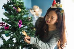 Chinese girl decorate Christmas tree. Asian Chinese woman with small santa costume decorate ornated objects on Xmas tree. Attractive cute girl celebrate stock images