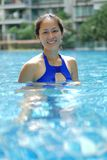 Asian Chinese Woman smiling confidently in swimming pool royalty free stock photo