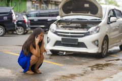 Asian Chinese woman in stress stranded on street suffering car engine failure having mechanic problem calling to insurance. Young desperate and upset Asian royalty free stock photography