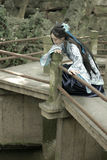 Asian Chinese woman in traditional Blue and white Hanfu dress, play in a famous garden Climb on the bent bridge Royalty Free Stock Photography