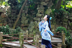 Asian Chinese woman in traditional Blue and white Hanfu dress, play in a famous garden on crooked Bridge Stock Photos