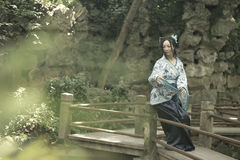 Asian Chinese woman in traditional Blue and white Hanfu dress, play in a famous garden on crooked Bridge Stock Image