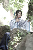 Asian Chinese woman in traditional Blue and white Hanfu dress, play in a famous garden ,sit on an ancient stone chair Royalty Free Stock Photos