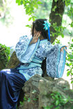 Asian Chinese woman in traditional Blue and white Hanfu dress, play in a famous garden ,sit on an ancient stone chair Stock Photo