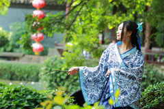 Asian Chinese woman in traditional Blue and white Hanfu dress, play in a famous garden ,sit on an ancient stone chair Stock Photos